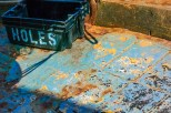 Conceptual – box of holes on the colorful deck of a fishing boat - labor
