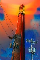 Fantasy – brick cellular smokestack with utility pole wires and colorful electric sky