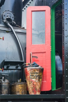 Man-Made – oilers beside red door of steam engine cockpit