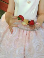 Life – Young girl in a pink dress delicately holds a strawberry from a plate of snacks
