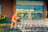 Conceptual – wet figure in raincoat pushes shopping carts i parking lot