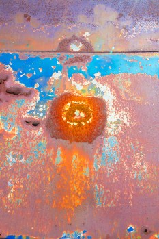 Graphic – image of rust spot 'sun' on peeling painted metal