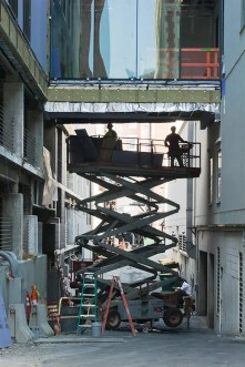 Man-Made – walkway between buildings being worked on by men on scissor lift