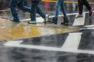 Conceptual – wet legs and feet cross a street crosswalk