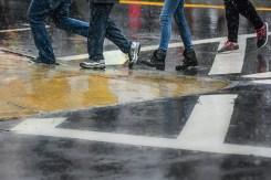 Conceptual – wet legs and feet cross a street crosswalk