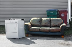 Conceptual – derelict washing machine and couch await trash pickup