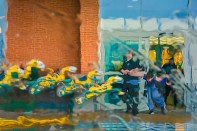 Fantasy – wet kiddie ride horses race past people on a rainy day