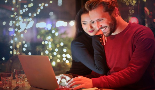 man and woman looking at computer screen together. Smiling