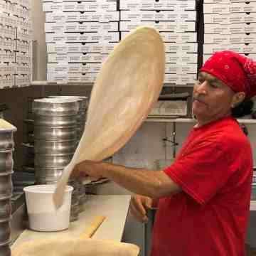 Long time employee (15 years) in red shirt (Carlos) tossing pizza dough at Pizza on 40th