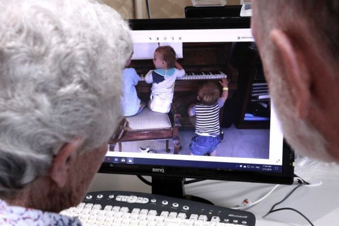 Two senior Australians look at a photo of young children playing the piano on a computer screen.