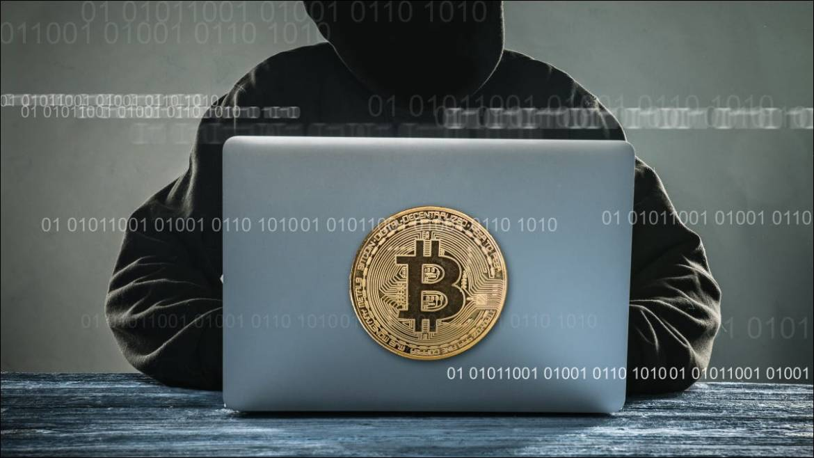 """A stylized anonymous """"hacker"""" using a laptop with a Bitcoin illustration."""