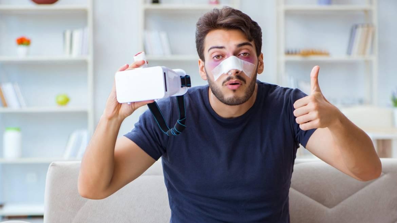 An injured man holding a VR headset