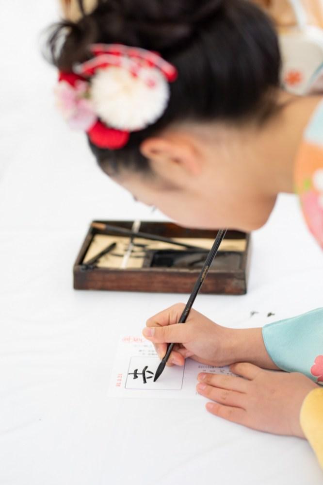 幸せという文字を書く、ご祈祷をする前の少女の写真