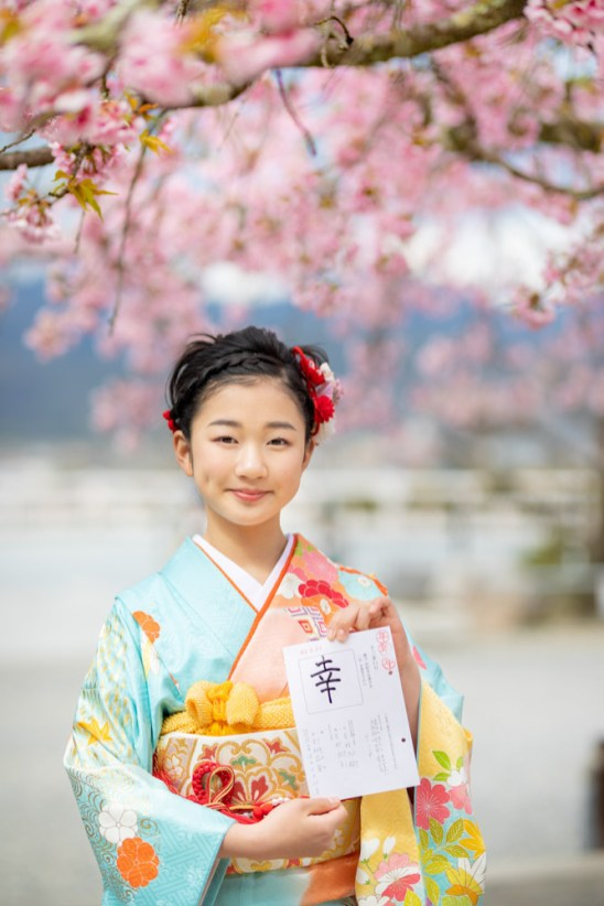 想いを込めた一文字を書いた紙を持って、桜の前で笑顔でポーズをとる女の子の写真