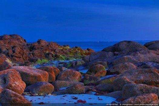 Premières lueurs de l'aube sur des rochers du Finistère à marée basse, recouverts d'algues, quelques minutes avant l'aube.
