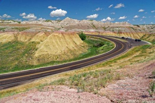 Une route au milieu de collines multicolores, dans le parc national des Badlands (Dakota du Sud, USA)
