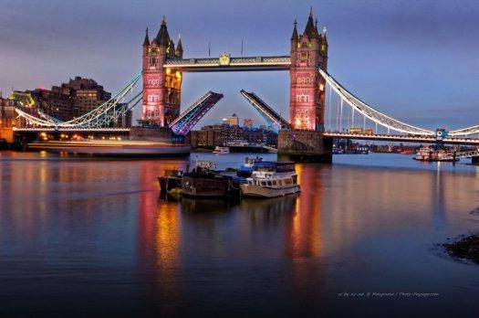 Trainées lumineuses laissées par un bateau circulant sur la Tamise et passant sous le Tower Bridge. Londres, Royaume-Uni
