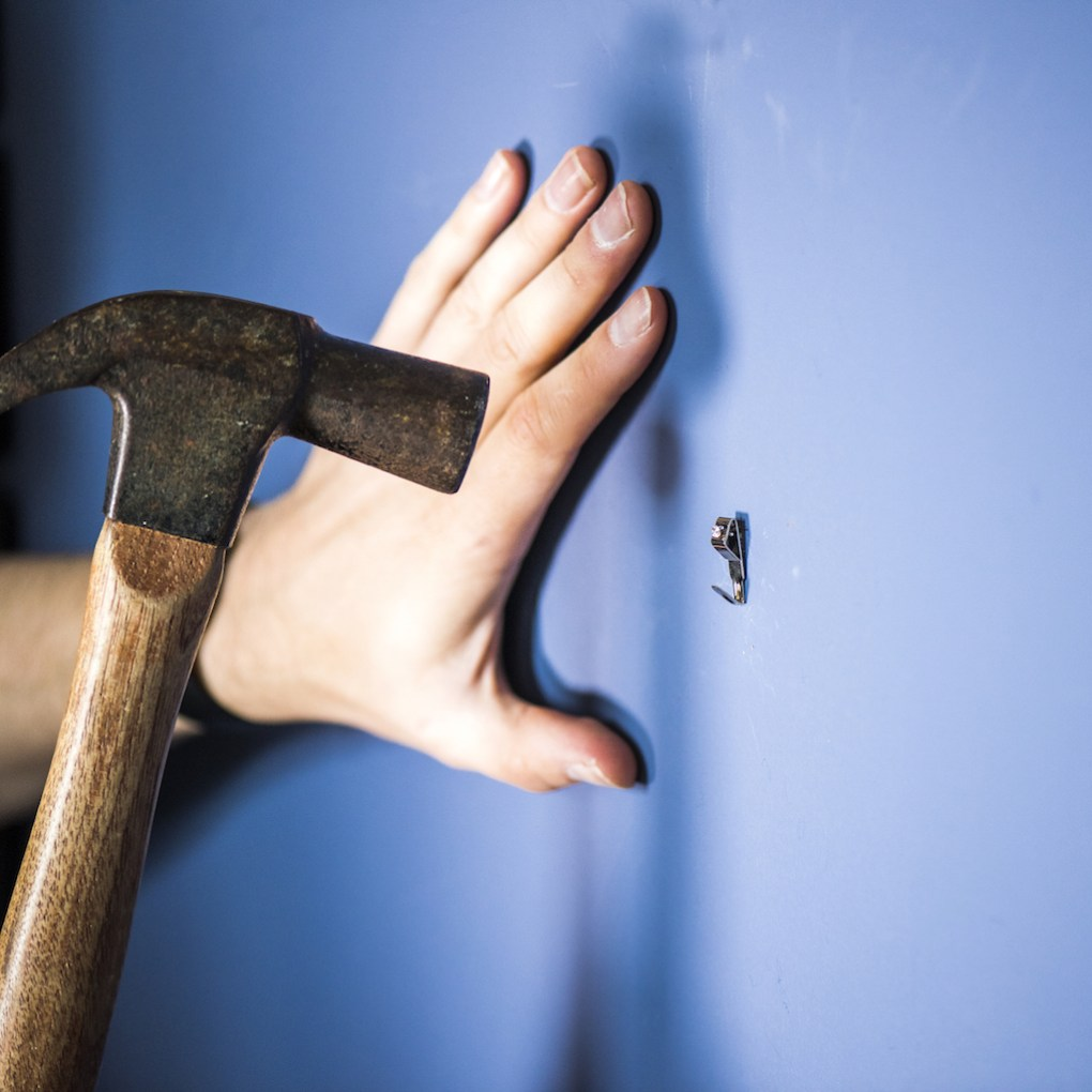 hammering a nail into a marked wall to hang a canvas