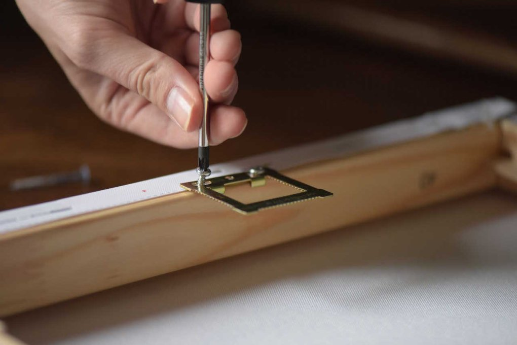 a hand screwing a bracket onto the back of a canvas