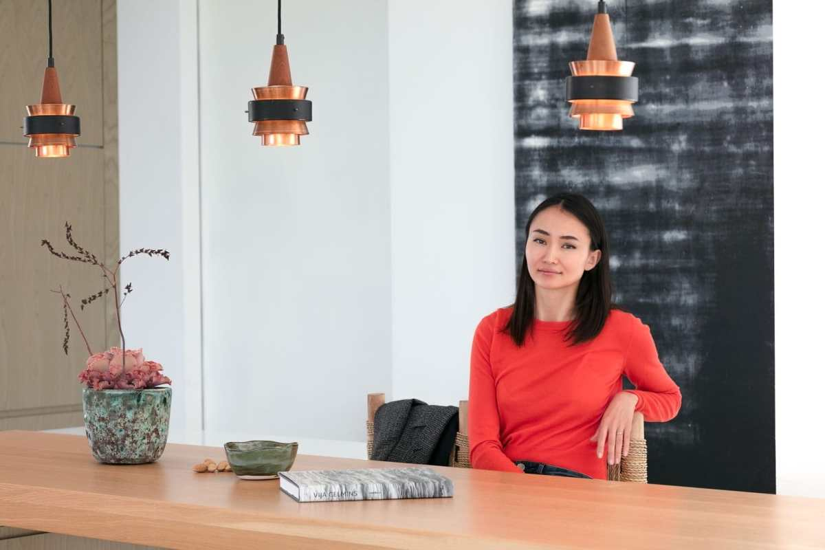 Entrevista fotográfica de mujer sonriente sentada en cocina de villa privada de Ibiza
