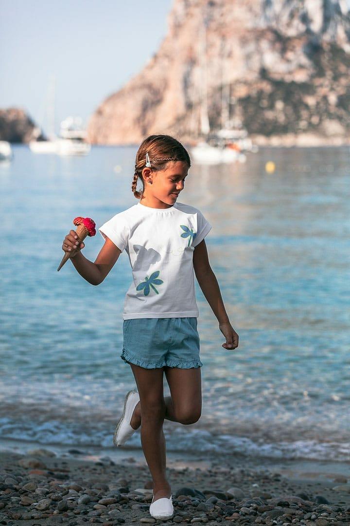 Fotografía de niña jugando en la orilla del mar vestida con ropa de verano