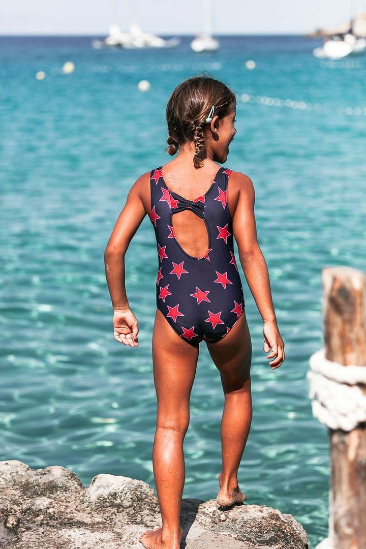 Fotografía instantanea de niña con traje de baño de marca infantil jugando en embarcadero de cala dort de Ibiza