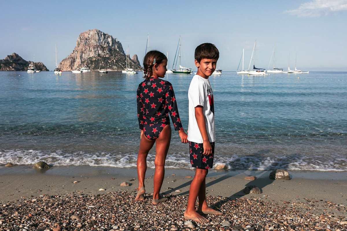 Imagen de dos niños posando en la orilla de la playa de Cala Dort de Ibiza