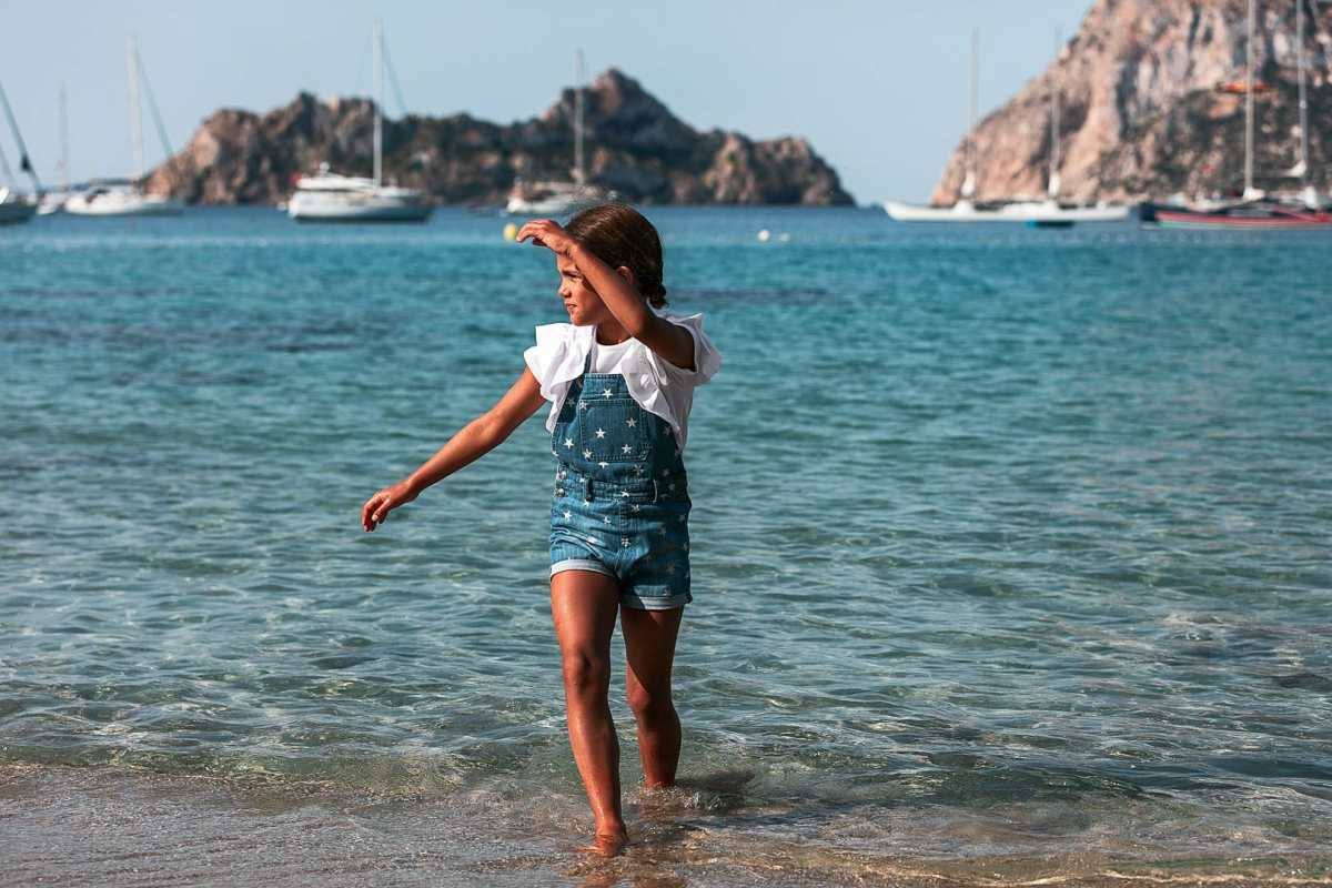 Reportaje fotográfico de ropa infantil con niña caminando en la orilla de la playa de cala Dort en Ibiza vestida con peto baquero