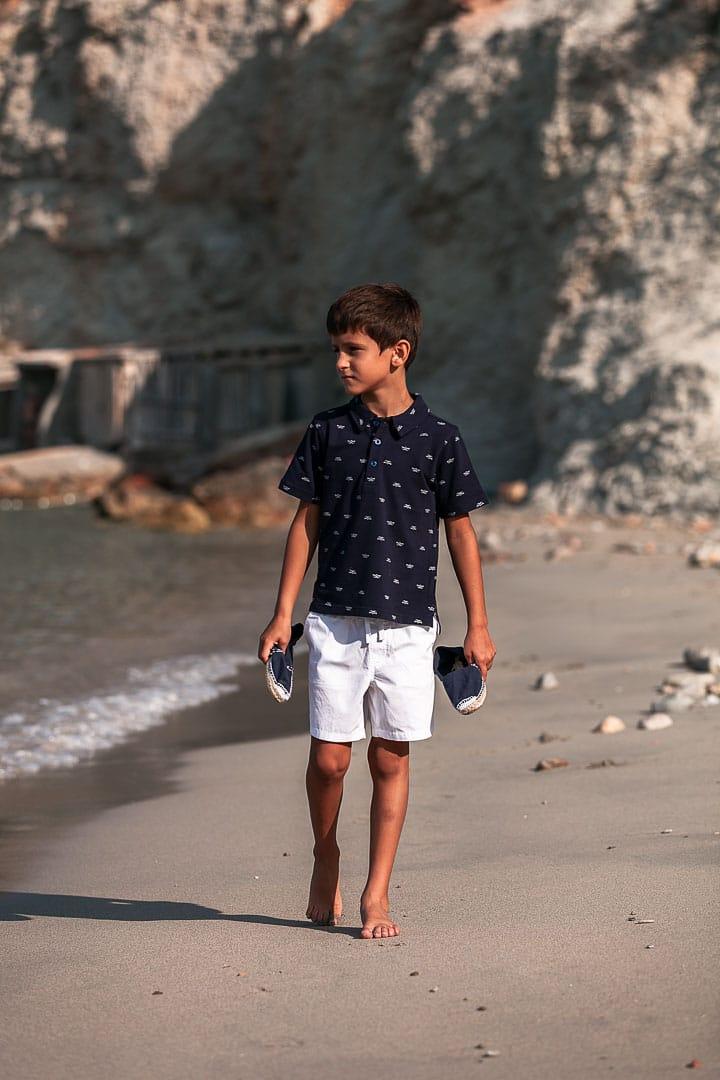 Reportaje fotográfico de ropa infantil con niño caminando en la orilla de la playa de cala Dort en Ibiza