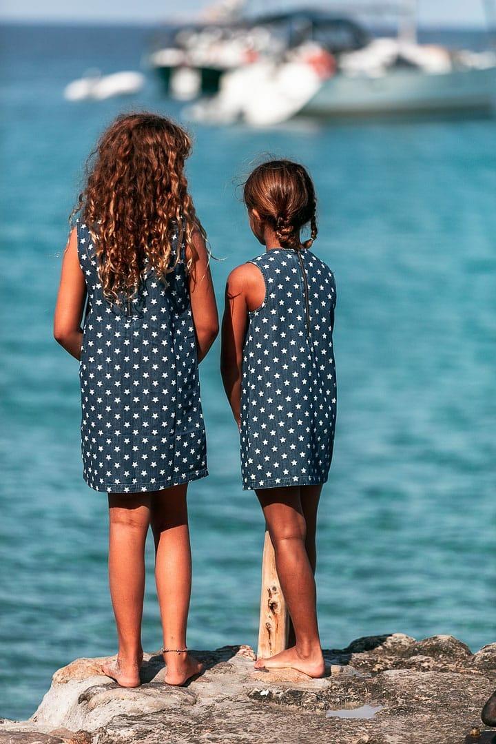 Retrato de dos niñas posando con ropa de marca infantil con el mismo vestido baquero en estampado de estrellas mirando al mar