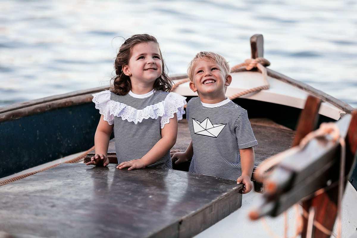 fotografía de dos niños sonrientes jugando sobre una barca vestidos con camiseta rayada de color azul en embarcadero de Ibiza