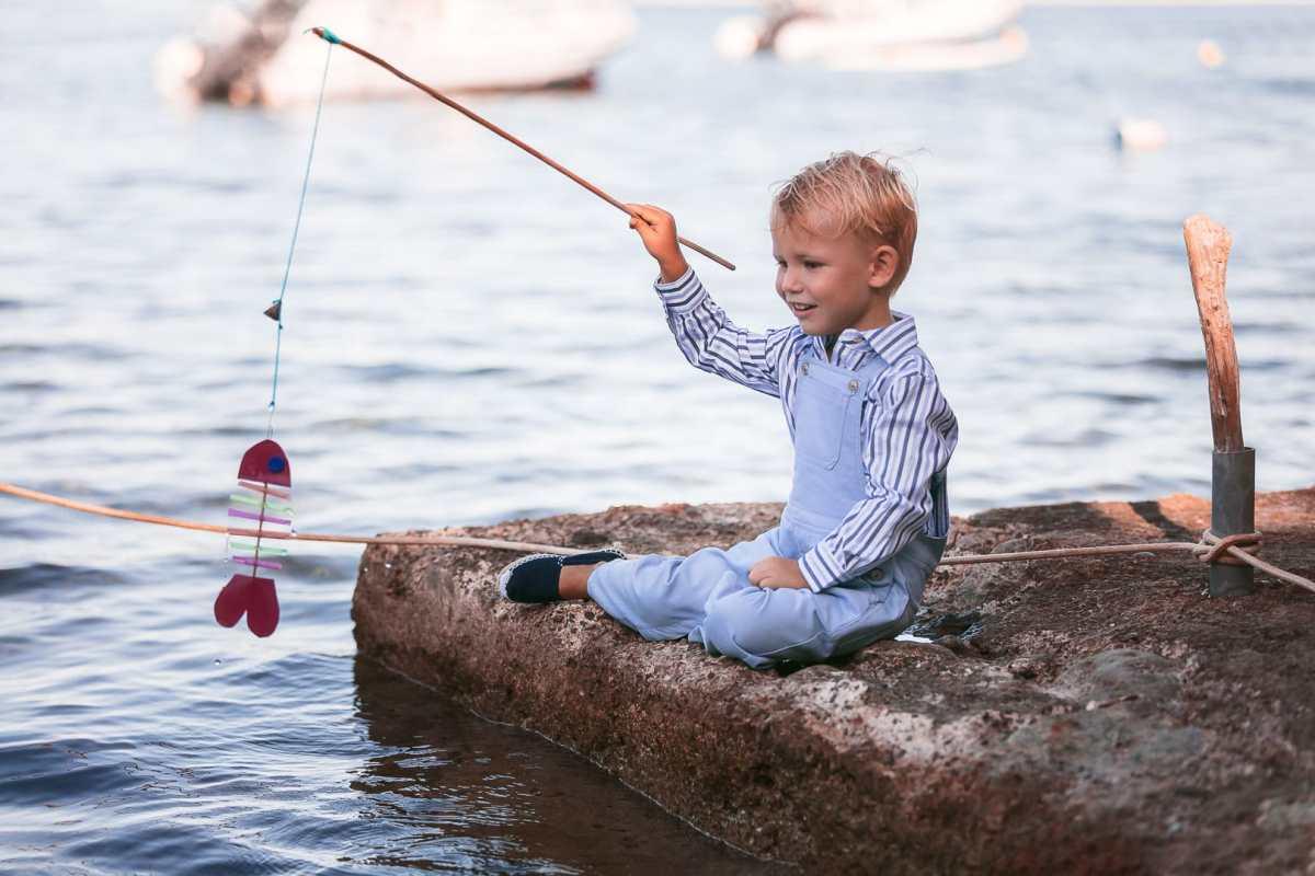 fotografía de ropa infantil con niño sentado con pantalón peto y camisa azulada jugando en embarcadero de Ibiza