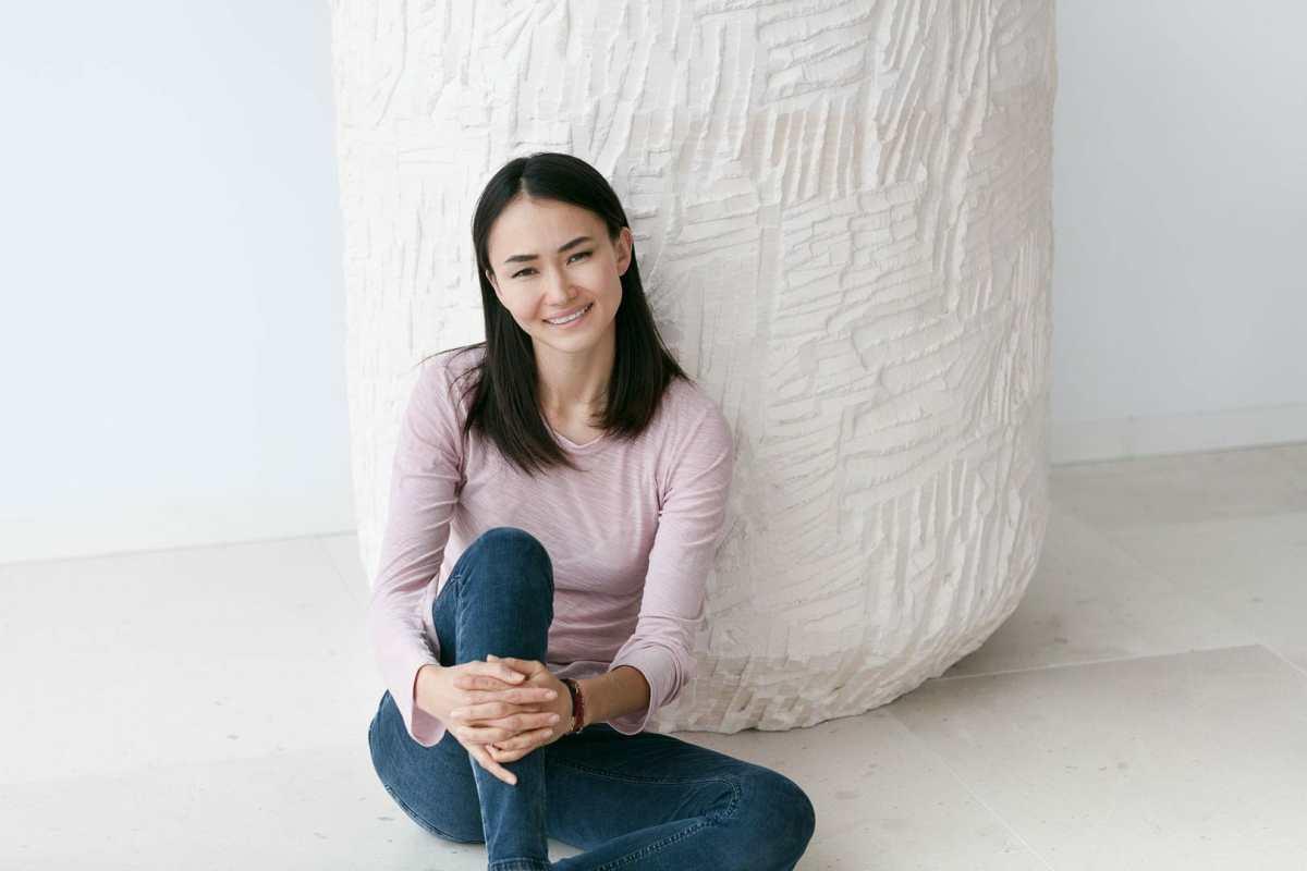 fotografía para entrevista de mujer sonriente sentada en el suelo de villa privada de Ibiza
