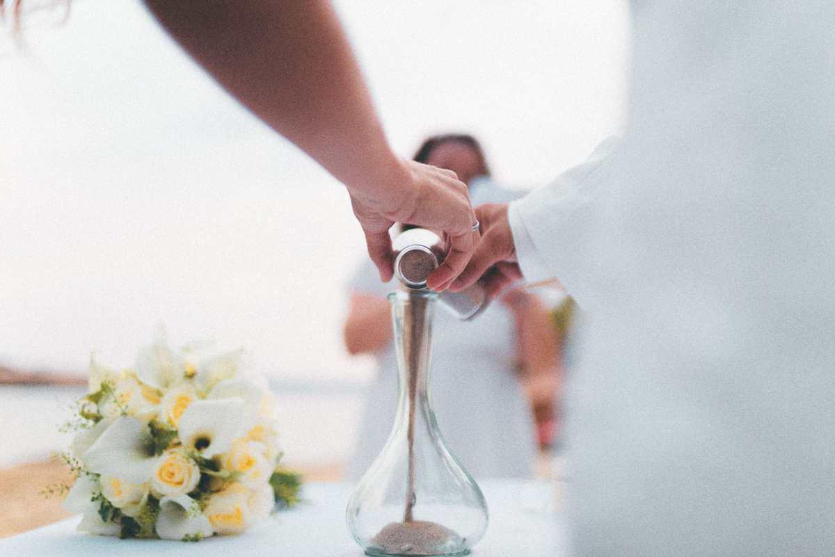 fotografia del momento en el que dos novios hechan arena en un jarron sobre una playa de cala comte