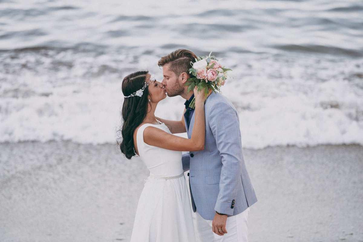imagen de novios besandose y posando sobre la orilla del puerto de sant miguel de ibiza