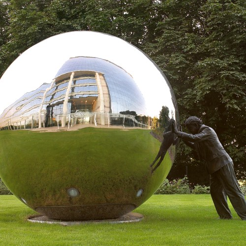 Statue of man pushing large chrome ball reflections of building sky grass - Exterior/Location photography
