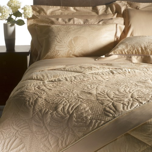 Close up of Sand coloured bedding and pillows with flowers on bedside table - Furniture photography