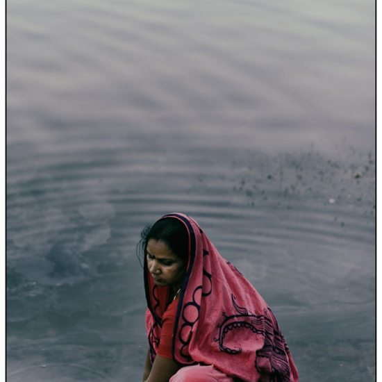 a woman washes clothes at dawn in the lake at udaipur