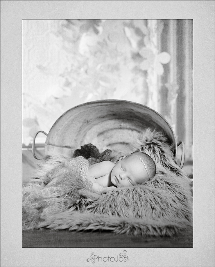 Sleeping newborn baby posed on side with a bucket