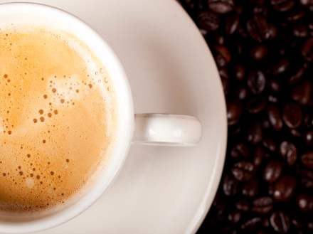 Top view of a cup of dark roasted coffee with coffeebeans in the background
