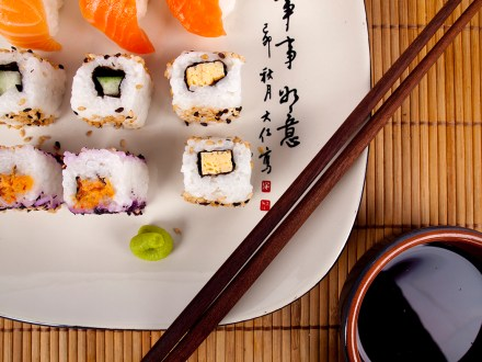 Fresh sushi and sashimi on a plate with chopsticks and soy sauce
