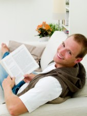 Young adult reading a book while he's lying on the couch