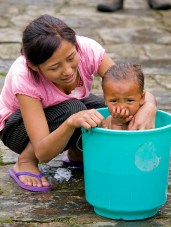 RABDENTSE, SIKKIM - October 2010: A young mother is washing her daughter in a bucket - October 2010 in Rabdentse, Sikkim, India