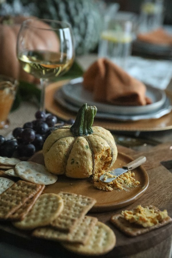 Pumpkin Shaped Cheddar Cheese Ball On Wood Plate With Crackers
