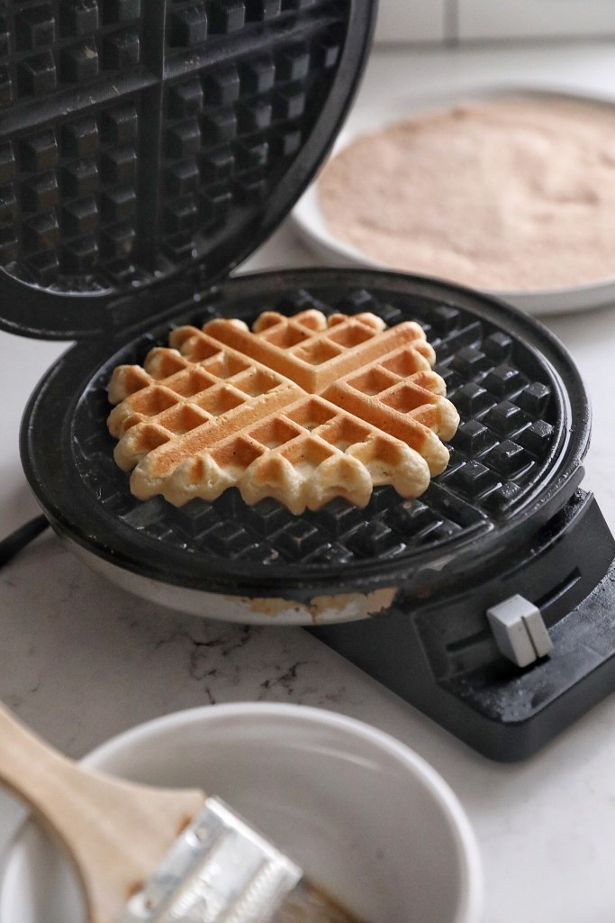Cooked waffle resting on the lower surface of an open waffle iron