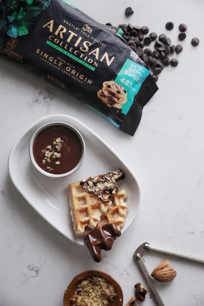 two chocolate dipped waffle quarters and small bowl of dark chocolate on a plate next to a small bowl of chopped walnuts and an open bag of chocolate chips