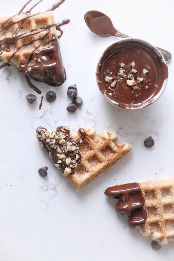 three waffle quarters dipped in and drizzled with dark chocolate, resting on white surface next to a small bowl of Nestle dark chocolate and a chocolate coated spoon