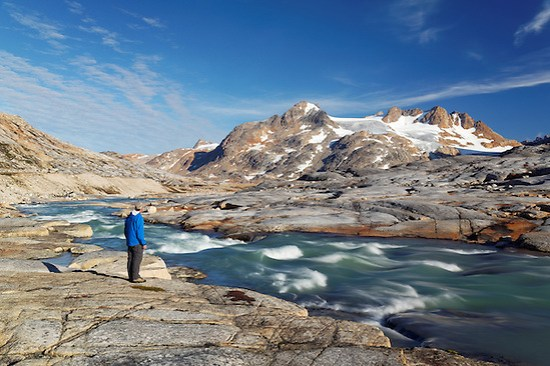 Hiker looking over glacial melt river and mountains, Sammileq Fjord, Ammassalik Island, East Greenland (Brad Mitchell)
