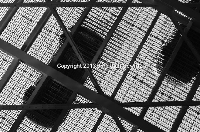 Black and white view from underneath of cars crossing a metal drawbridge. (Jonathan.Gewirtz@gmail.com)