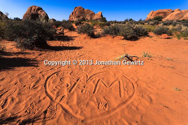 Graffiti and footsteps in the sandy desert floor at Arches National Park, Utah. (Jonathan Gewirtz   jonathan@gewirtz.net)